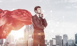 Concept of power and sucess with businessman superhero in big ci. Young pensive businessman wearing red cape against modern city background royalty free stock images