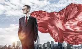 Concept of power and sucess with businessman superhero in big city. Young confident businessman wearing red cape against modern city background stock photos
