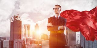 Concept of power and sucess with businessman superhero in big city. Young confident businessman wearing red cape against modern city background stock images