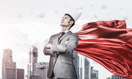 Concept of power and sucess with businessman superhero in big city. Young confident businessman wearing red cape against modern city background stock photo