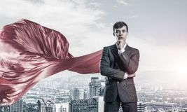 Concept of power and sucess with businessman superhero in big city. Young pensive businessman wearing red cape against modern city background stock photo