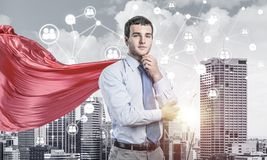Concept of power and sucess with businessman superhero in big city. Young pensive businessman wearing red cape against modern city background royalty free stock photo