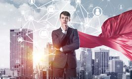 Concept of power and sucess with businessman superhero in big city. Young pensive businessman wearing red cape against modern city background royalty free stock photography