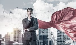 Concept of power and sucess with businessman superhero in big city. Young pensive businessman wearing red cape against modern city background stock photos