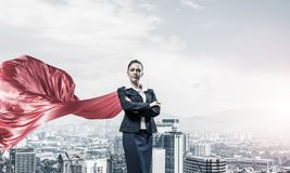 Concept of power and sucess with businesswoman superhero in big. Young confident businesswoman wearing red cape against modern city background Stock Photos