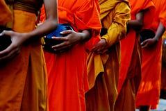 Concept prêté bouddhiste utilisant : Moines dans des robes longues rassemblant l'aumône photographie stock