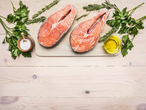 Concept preparation raw salmon steak with herbs, parsley, olive oil and salt on vintage cutting board wooden rustic background Stock Photos