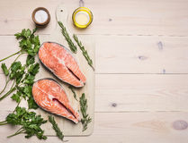 Concept preparation raw salmon steak with herbs, parsley, olive oil and salt on vintage cutting board wooden rustic background. Concept preparation raw salmon Royalty Free Stock Image