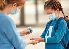 Concept of preventing a coronavirus covid-19 and viral infections. Mother treats her child`s hands with a sanitizer before school