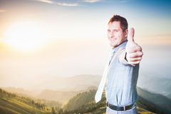 Concept of professional career and future plans in business. Image of successful happy businessman at top of mountain looking at camera with thumbs up gesture Royalty Free Stock Images
