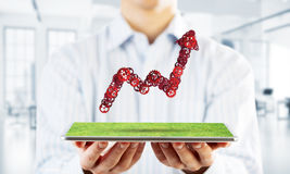 Concept of progress and income in business presented by going up arrow. Close of businessman holding tablet with progressing graph. Mixed media Stock Photography