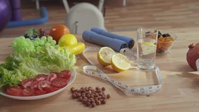Concept of proper nutrition ,on the table are dumbbells measuring tape vegetables fruits and nuts