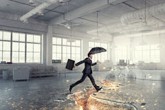 Concept of protection from crisis and trouble . Mixed media. Businessman with umbrella overcome challenge in chaos office. Mixed media Stock Images