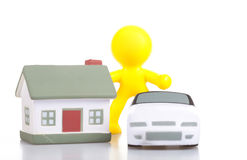 The concept of purchase of real estate. One toy little man costs near to the house and the car. The concept of purchase of real estate royalty free stock photography