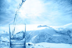 Concept purity of blue water in transparent glass over winter la. Ndscape of mountains higher than clouds, close up Royalty Free Stock Images