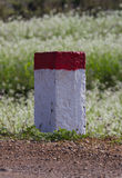 Concept of purpose and target. Red and white painted milestones in range on a country road under the sunlight. Concept of purpose and target, long term and the Royalty Free Stock Photos
