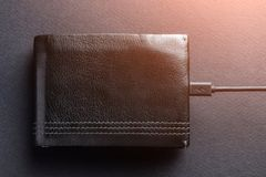 Concept. The purse is charged with money through the charging ca. Ble for the phone. Lights, tinted stock photography