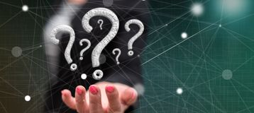 Concept of question. Question concept above the hand of a woman in background stock images