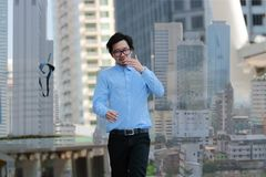 Concept réussi d'affaires Double exposition du jeune homme d'affaires asiatique heureux marchant et jetant sa cravate dans c de c images stock