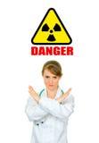 Concept-radiation hazard! Doctor with crossed arms. Concept-radiation hazard! Serious medical female doctor with crossed arms isolated on white. Forbidden stock photo