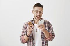 Concept rapide et commode d'opérations bancaires Portrait d'étudiant masculin attirant heureux et enthousiasmé dans l'équipement  photographie stock