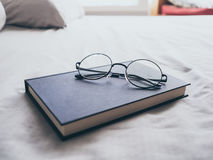 Eyeglasses and book in bedroom for reading and relax. stock photo