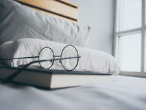Eyeglasses and book in bedroom for reading and relax. stock image