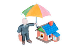 The concept of real estate insurance. Plasticine man with an umbrella and a small house Stock Image