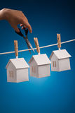 Three paper houses on washing line. Three paper houses pegged to a washing line with a hand holding a scissor about to cut the line on blue background Royalty Free Stock Photos