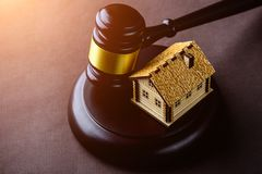 Concept of realty and law. Little wooden house and judges gavel. On the table in rays of the sun royalty free stock photos