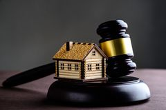 Concept of realty and law. Little wooden house and judges gavel. On the table stock photo