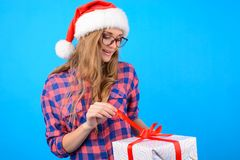 Concept of receiving presents on Christmas Day. Cheerful smiling. Woman in checkered shirt, santa hat and spectacles is opening box in her hands by touching the Stock Photo