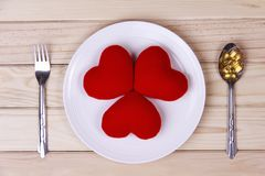 Concept red heart on plate with body tonic on spoon and fork on. Wood background.Health care yourself should be done stock photos