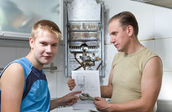 The concept of relations in a family. The father a. Nd the son-teenager together look the instruction on repair a gas water heater royalty free stock image