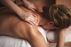 Young lady having oil massage in spa salon. Concept of relaxation and body care. Top angle portrait of female therapist making massage of upper back with royalty free stock photography
