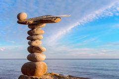 Concept of relaxation and calmness. Feather and stone in balance on seashore royalty free stock photo