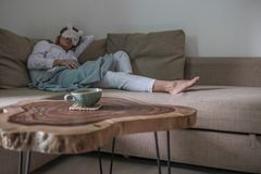 Young woman is having a rest on the beige couch stock image