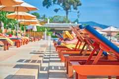 Concept of relaxing sunbathing by the water. Sun loungers by the outdoor pool. Sunny summer afternoon. Prospect. Copy space. royalty free stock image