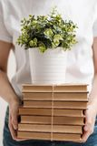 The concept of relocation and moving to a new home. Close-up, female hands hold a pile of books and a green plant in a royalty free stock image