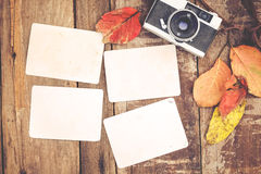Concept of remembrance and nostalgia in fall season. Retro camera and empty old instant paper photo album on wood table with maple leaves in autumn border Royalty Free Stock Photos