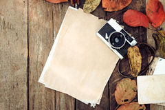 Concept of remembrance and nostalgia in fall season. Retro camera and empty old instant paper photo album on wood table with maple leaves in autumn border Royalty Free Stock Images
