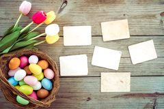Concept of remembrance and nostalgia holiday in spring. Colorful Easter eggs in nest with flower and empty old paper photo album on wood table - concept of royalty free stock photography