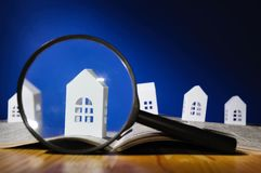 Concept of rent, search, purchase real estate. Magnifying glass in front of an open newspaper with paper houses. Concept of rent, search, purchase real estate stock photos