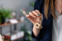 Concept of renting an apartment. House key in womans hands. Young woman. Modern light lobby interior. Real estate royalty free stock image