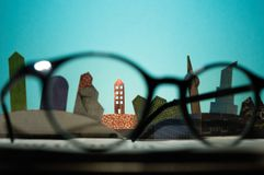 The concept of renting, searching, buying real estat. Glasses in front of an open newspaper with paper houses. The concept of renting, searching, buying real royalty free stock photography
