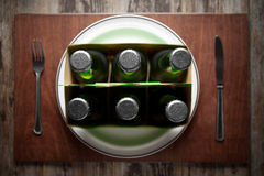Concept representing Alcoholism on a funny way. Conceptual image representing alcoholism on a funny way using a six-pack of beer bottles for dinner Stock Image