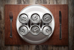 Concept representing Alcoholism on a funny way. Conceptual image representing alcoholism on a funny way using a six-pack of beer cans for dinner Stock Photo