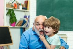 Concept of a retirement age. Cute little preschool kid boy with Grandfather in a classroom. Portrait of grandfather and stock photos
