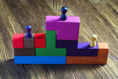 The concept of rewarding on a pedestal, victories and achievemen. Ts. Three wooden toy figures on the podium. Persons standing on the podium Royalty Free Stock Photo