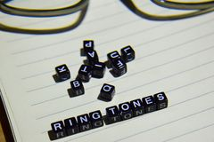 Concept of Ring Tones on wooden cubes with glass eye, books in Vintage background stock photos